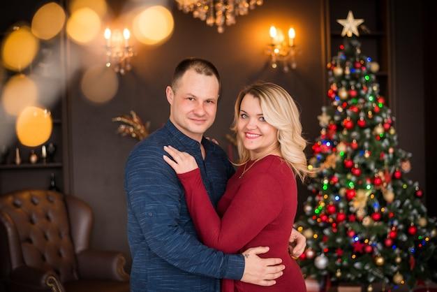 메리 크리스마스, 해피 홀리데이. 가족, 한 남자와 크리스마스 트리 배경에 여자의 초상화. 새해 복 많이 받으세요