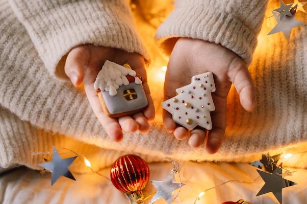 С рождеством и праздником. пряники в руке ребенка. ожидание рождества.