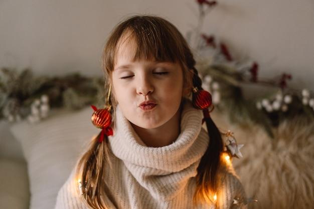 메리 크리스마스, 해피 홀리데이. 소녀는 공기 키스를 제공합니다. 크리스마스를 기다리고 있습니다.