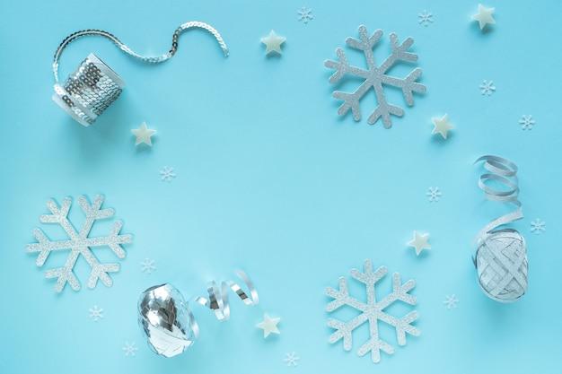 メリークリスマスとハッピーホリデーのグリーティングカード、フレーム、バナー、フラットレイ。新年。クリスマス、ノエル白、青い背景の上面図に銀の装飾品。冬のクリスマスの休日のテーマ、コピースペース