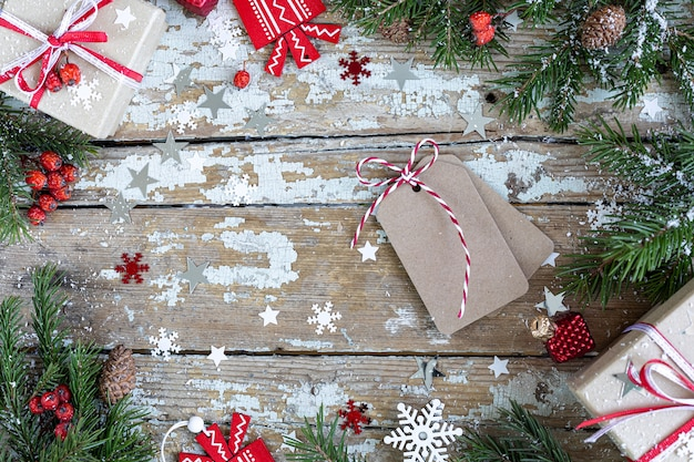 メリークリスマスとハッピーホリデーのグリーティングカード、フレーム、バナー。新年。木製の背景に雪と年賀状。冬のクリスマスの休日のテーマ。フラットレイ。コピースペース