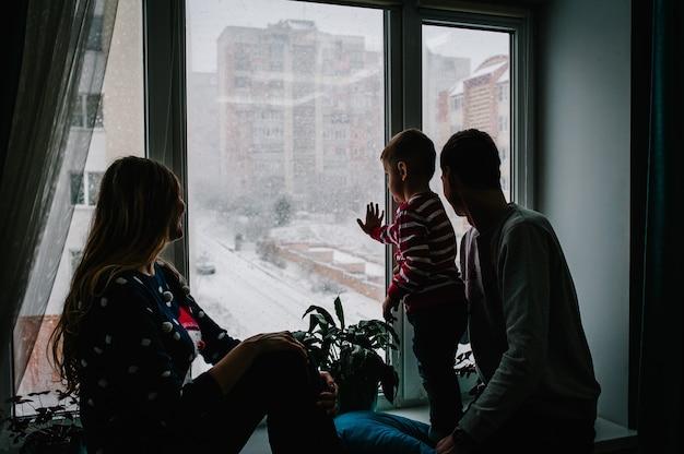 С рождеством и праздником! счастливая семья: мама, папа и маленький сын в свитерах санта-клауса, сидя на окне и глядя на зимний парк. комната украшена на рождество. наслаждайтесь снегопадом.