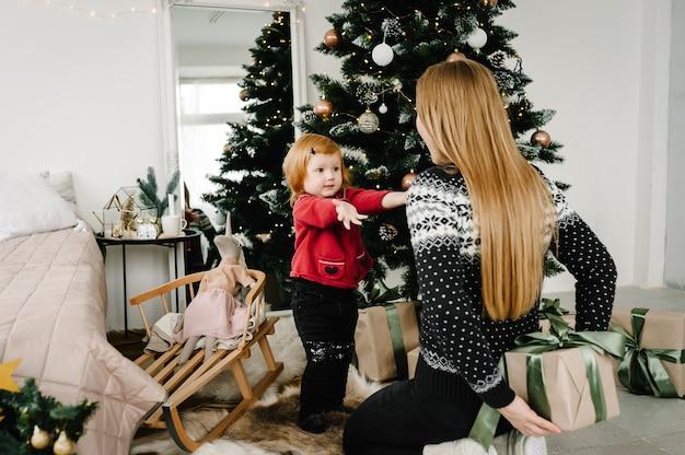 С рождеством и праздником мама дарит дочке подарок возле елки