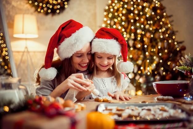 Счастливого рождества и счастливых праздников. мать и дочь приготовления рождественского печенья.