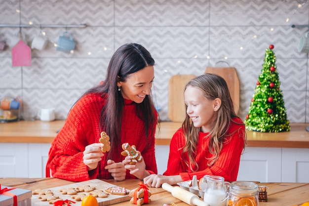 メリークリスマスとハッピーホリデー。母と娘がクッキーを調理します。