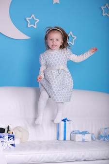 메리 크리스마스, 해피 홀리데이. 새해 . 크리스마스와 흰색 소파에 어린 소녀의 초상화를 제공합니다. 새해 휴일 개념. 벽에 하얀 달과 푸른 벽.