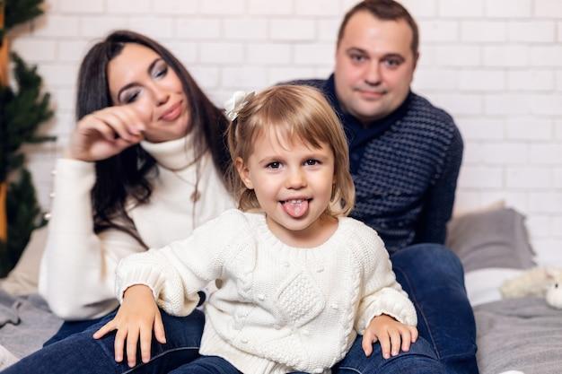 즐거운 성탄절과 즐거운 휴일 보내세요. 부모와 어린 딸아이는 실내에서 크리스마스 트리 근처에서 즐겁게 놀고 있습니다.