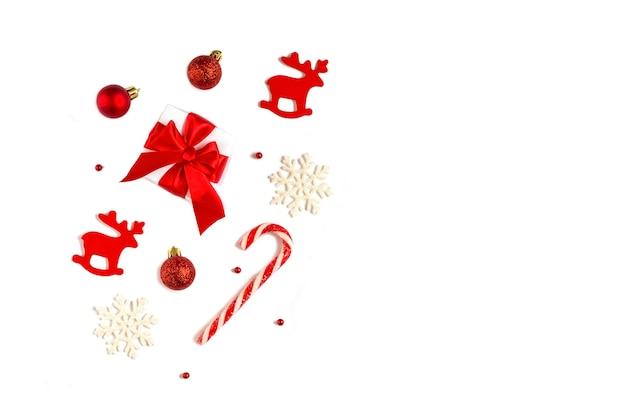 メリークリスマスとハッピーホリデーのポストカード、フレーム。新年。クリスマスの装飾が施された白い背景のギフトボックス。冬の休日のテーマ。フラットレイ。