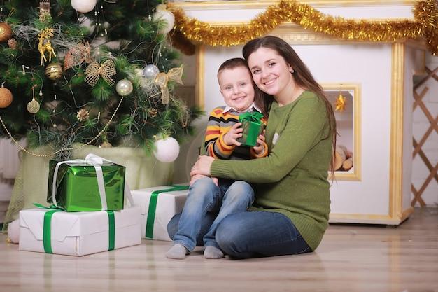 С рождеством и праздником. довольно молодая мама с ее забавным маленьким сыном возле елки с подарочными коробками в помещении.