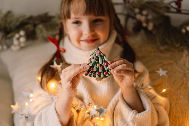 メリークリスマスとハッピーホリデー。子供はジンジャーブレッドクッキーで遊んでいます。クリスマスを待っています。