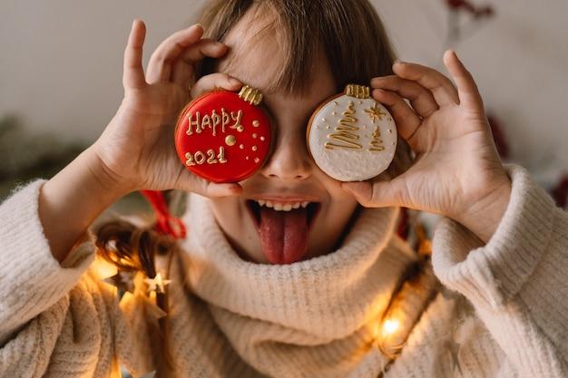 С рождеством и праздником. ребенок играет с пряниками. ожидание рождества.