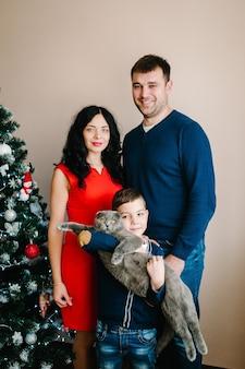 С рождеством и праздником! молодая семья празднует рождество дома возле елки. счастливые мама, папа и сын наслаждаются отдыхом вместе.