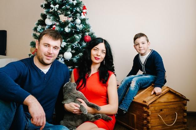 메리 크리스마스, 해피 홀리데이! 크리스마스 트리 근처 집에서 크리스마스를 축 하하는 젊은 가족. 행복한 엄마, 아빠와 아들이 함께 휴가 시간을 즐기고 있습니다.