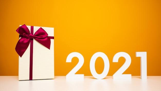 メリークリスマスと新年あけましておめでとうございます2021年のテーブルと黄色のギフトボックスのモックアップ。