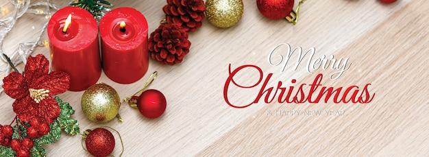 소셜 미디어 웹사이트 또는 팬 페이지 장식의 머리나 표지를 위한 메리 크리스마스와 새해 복 많이 받으세요. 나무 배경에 불꽃과 크리스마스 장식 소품이 있는 빨간 촛불.