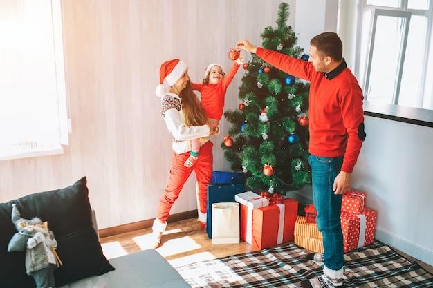 メリークリスマス、そしてハッピーニューイヤー。クリスマスツリーに立っている若い家族の美しく明るい写真。男は赤いおもちゃと笑顔を持っています。子供は興味を持ってそれに到達します。