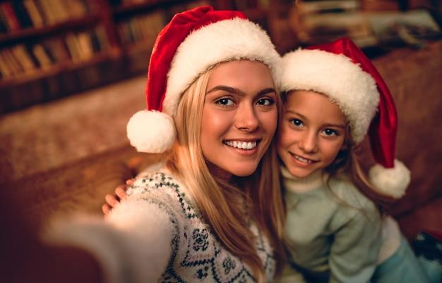 Веселого рождества и счастливого нового года! красивая мама и дочь в шляпах санты делают селфи с помощью смартфона и улыбаются во время празднования.