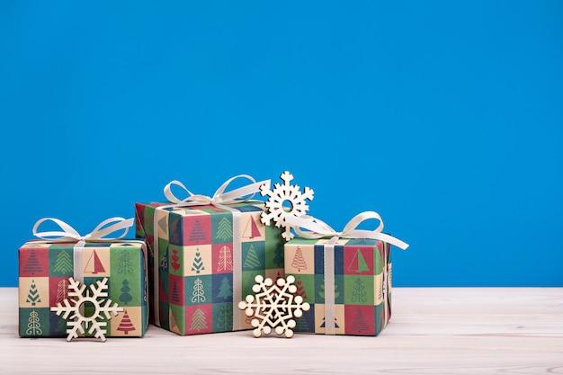 Веселого рождества и счастливого нового года. яркие коробки с лентами и деревянными снежинками на светлом деревянном фоне.