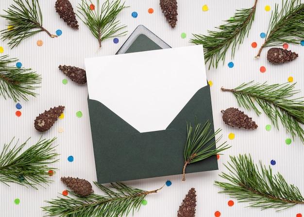 봉투에 기쁜 성 탄과 새 해 복 많이 받으세요 카드. 흰색 메모지 시트. 소나무 가지, 원뿔 및 축제 색종이로 장식