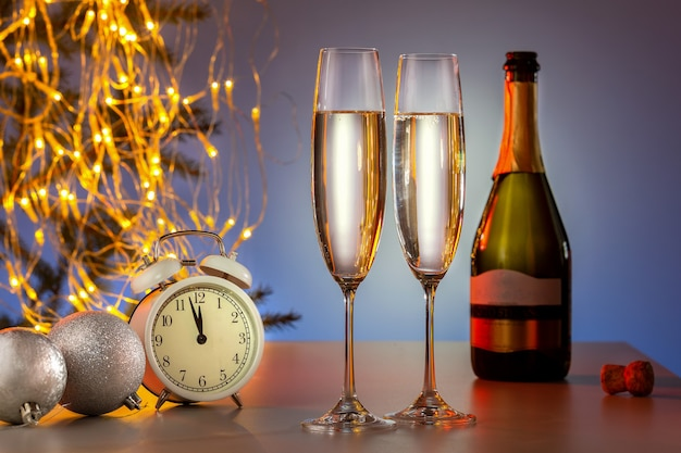 Веселого рождества и счастливого нового года. шампанское и новогоднее украшение с винтажными часами и праздничными огнями.