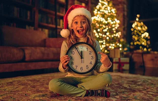 즐거운 성탄절 보내시고 새해 복 많이 받으세요! 매력적인 어린 소녀가 손에 시계와 함께 집에 앉아 새해까지 5 분 동안 웃고 있습니다.