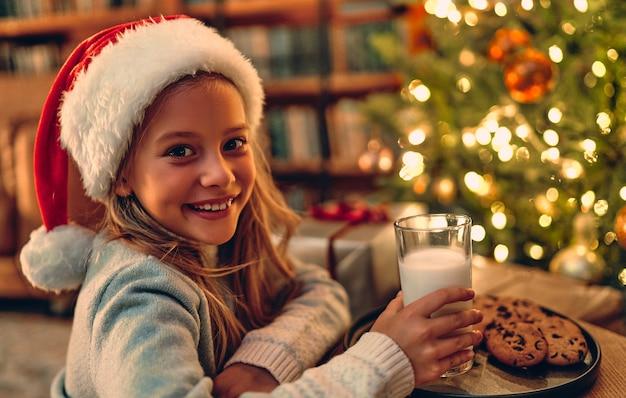 Веселого рождества и счастливого нового года! очаровательная маленькая девочка приготовила санту стакан молока и печенья.