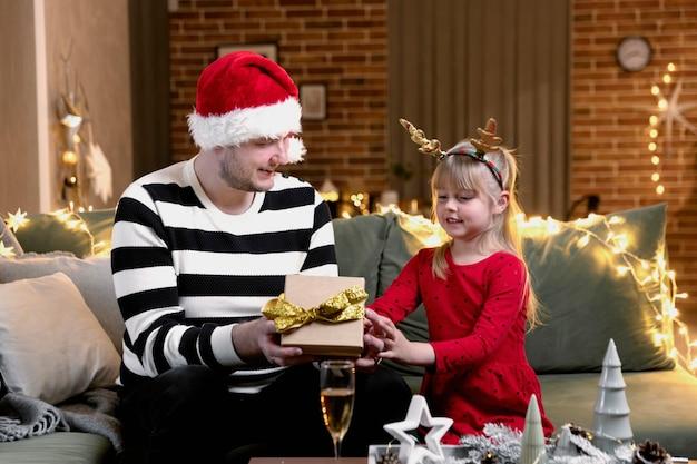 メリークリスマス、そしてハッピーニューイヤー。クリスマスプレゼントサプライズ。小さな幸せな笑顔の娘の女の子がプレゼントを開きます。お祝いのクリスマスの装飾が施された家の中でギフトボックスを持って屋内で贈る父