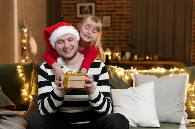 メリークリスマス、そしてハッピーニューイヤー。クリスマスプレゼントサプライズ。休日のために飾られた家の屋内で贈り物を持って父を抱き締める小さな笑顔の娘の女の子。ハンサムな男はギフトボックスを保持しています
