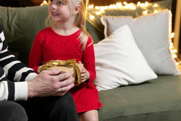 メリークリスマス、そしてハッピーニューイヤー。クリスマスプレゼントサプライズ。小さな娘の女の子は驚いてクリスマスプレゼントを受け取ります。父は娘に手元に贈り物をします。自宅でギフトボックスを屋内に保持する