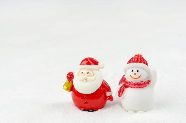 メリークリスマスと新年あけましておめでとうございますのコンセプト。かわいいサンタクロースの図とコピースペースと雪の上の木