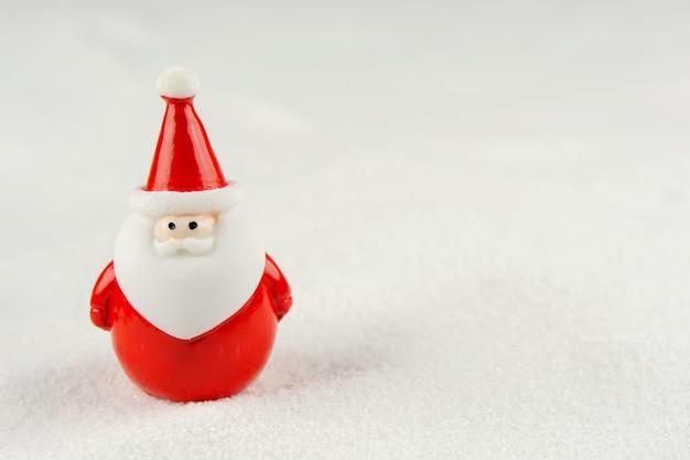 メリークリスマスと新年あけましておめでとうございますのコンセプト。コピースペースと雪の上のかわいいサンタクロースの図