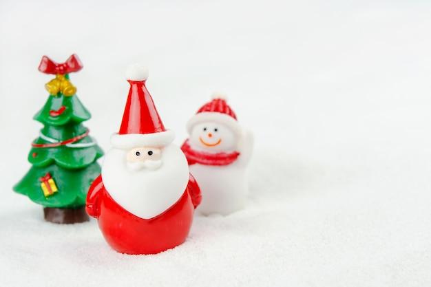 メリークリスマスと新年あけましておめでとうございますのコンセプト。かわいいサンタクロース、雪だるまの姿とコピースペースと雪の上の木