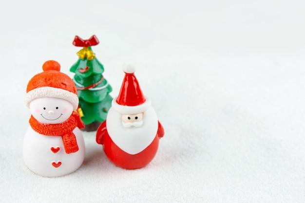 기쁜 성 탄과 새 해 복 많이 받으세요 개념입니다. 귀여운 산타 클로스, 눈사람 그림 및 복사 공간이 있는 눈 위에 있는 나무