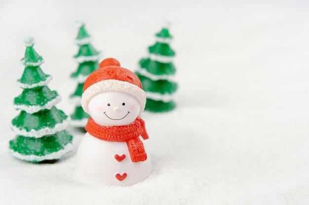 기쁜 성 탄과 새 해 복 많이 받으세요 개념입니다. 복사 공간이 있는 눈 위의 귀여운 눈사람 그림과 나무