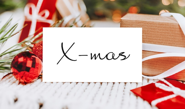 Счастливого рождества и счастливого нового года концепция с подарочными коробками и поздравительной открыткой с текстом x-mas