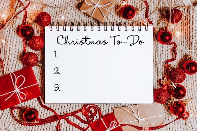 Счастливого рождества и счастливого нового года концепция с подарочными коробками, игрушками и блокнотом с текстом рождества to-do