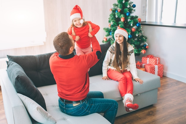 メリークリスマス、そしてハッピーニューイヤー。ソファに座っている幸せな家族の楽しい写真。お父さんは子供と遊ぶ。彼は女の子を手に持っている。彼女は微笑みます。子供は幸せです。彼女は帽子をかぶっている。女性はそれらを見てください。