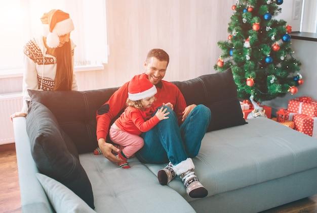 즐거운 성탄절 보내시고 새해 복 많이 받으세요. 가족 사진. 젊은 남자가 딸과 함께 소파에 앉아