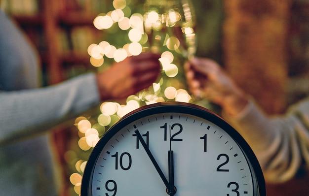 즐거운 성탄절 보내시고 새해 복 많이 받으세요! 새해까지 5분. 크리스마스 트리와 안경을 낀 두 손을 배경으로.