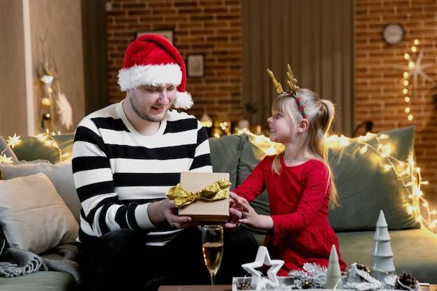 メリークリスマス、そしてハッピーニューイヤー。ギフトサプライズ。小さな幸せな笑顔の娘の女の子は驚いてクリスマスプレゼントを開きます。父はお祭りの装飾が施された家の屋内で娘に贈り物をします