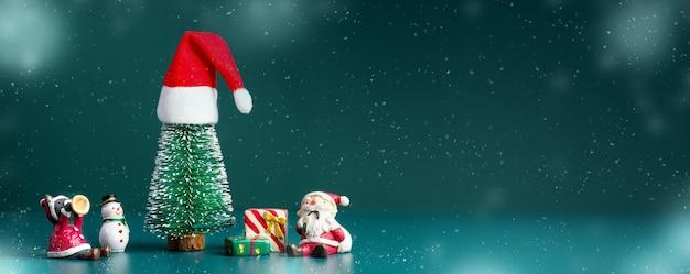 메리 크리스마스와 새해 복 많이 받으세요 빛나는 눈이 크리스마스 트리에 산타 모자와 짙은 녹색 배경에 산타 클로스, 눈사람 및 선물 상자가 있습니다. 디자인 또는 제품 표시를 위한 배너