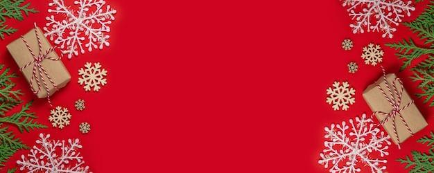 Поздравительная открытка с рождеством и новым годом. новогодний фон с подарками и зелеными еловыми ветками. состав рождественских праздников на красном фоне с копией пространства. плоская планировка. длинный широкий баннер Premium Фотографии