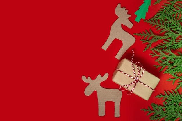 Поздравительная открытка с рождеством и новым годом. новогодний фон с рождественскими подарками и зелеными еловыми ветками. состав рождественских праздников на красном фоне с копией пространства. плоская планировка, вид сверху