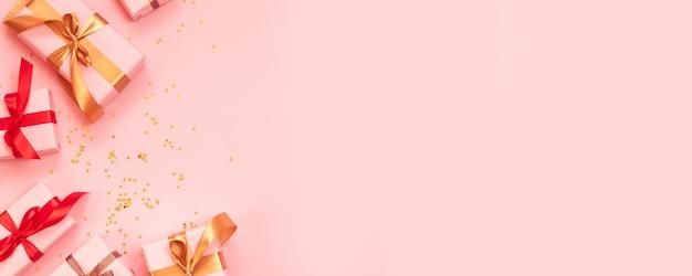 Открытка с новым годом и рождеством с бумажной подарочной коробке, золотой лук красной лентой и блеск конфетти на розовом фоне.