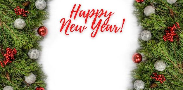 トウヒの枝の赤と緑のボールとメリークリスマスと新年あけましておめでとうございますグリーティングカード