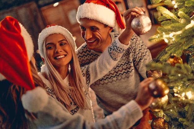 즐거운 성탄절 보내시고 새해 복 많이 받으세요! 집에서 겨울 휴가를 축하하는 행복한 가족. 엄마, 아빠와 딸이 새해 나무를 장식합니다.