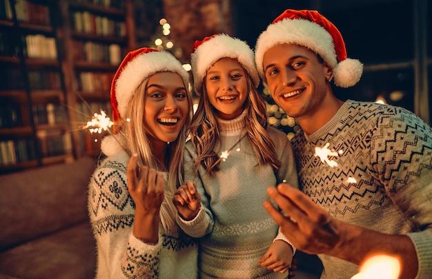 Веселого рождества и счастливого нового года! счастливая семья празднует зимний праздник дома. родители и их дочь ждут рождества в шляпах санты с бенгальскими огнями в руках.