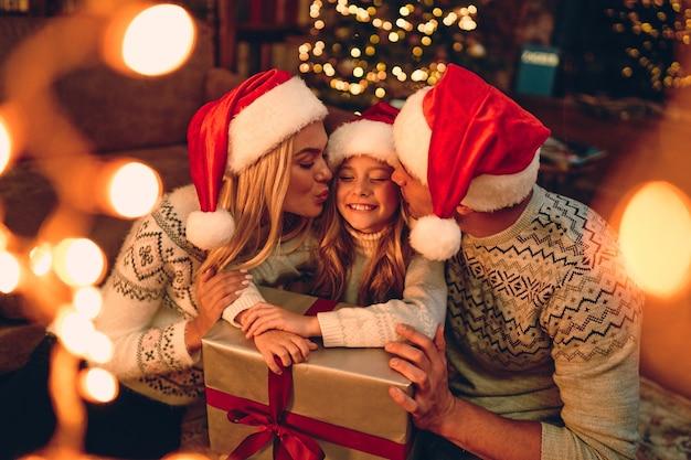 Веселого рождества и счастливого нового года! счастливая семья в ожидании нового года в шапках деда мороза обменивается подарками друг с другом. мама и папа целуют симпатичную дочку
