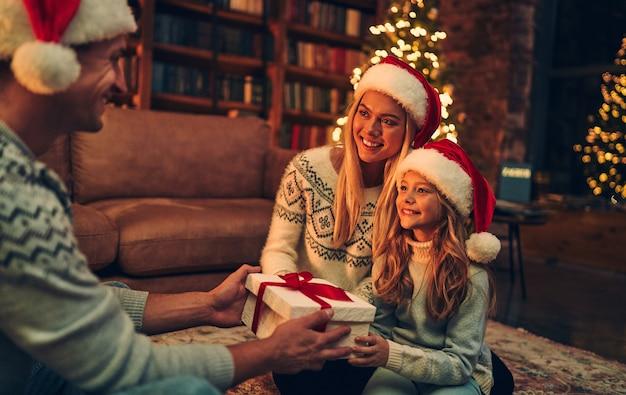 メリークリスマス、そしてハッピーニューイヤー!幸せな家族はサンタクロースの帽子で新年を待っていますお互いに贈り物を交換します。