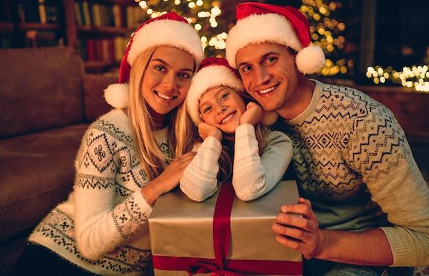 즐거운 성탄절 보내시고 새해 복 많이 받으세요! 행복한 가족은 산타 클로스 모자에서 새해를 기다리고 있으며 서로 선물을 교환합니다.